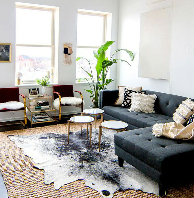 layering-rugs-cowhide-over-seagrass-living-room-Shelby-Girard-via-Domaine