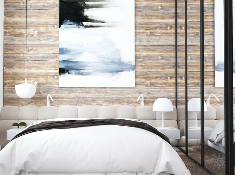 feature wall with original art above a neutral bed