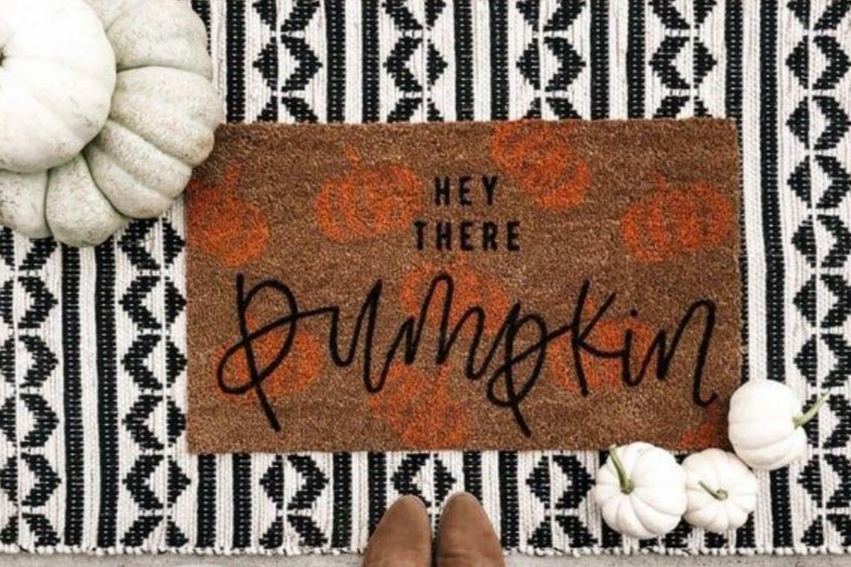 Welcoming Thanksgiving door décor doormat that reads, Hey there pumpkin