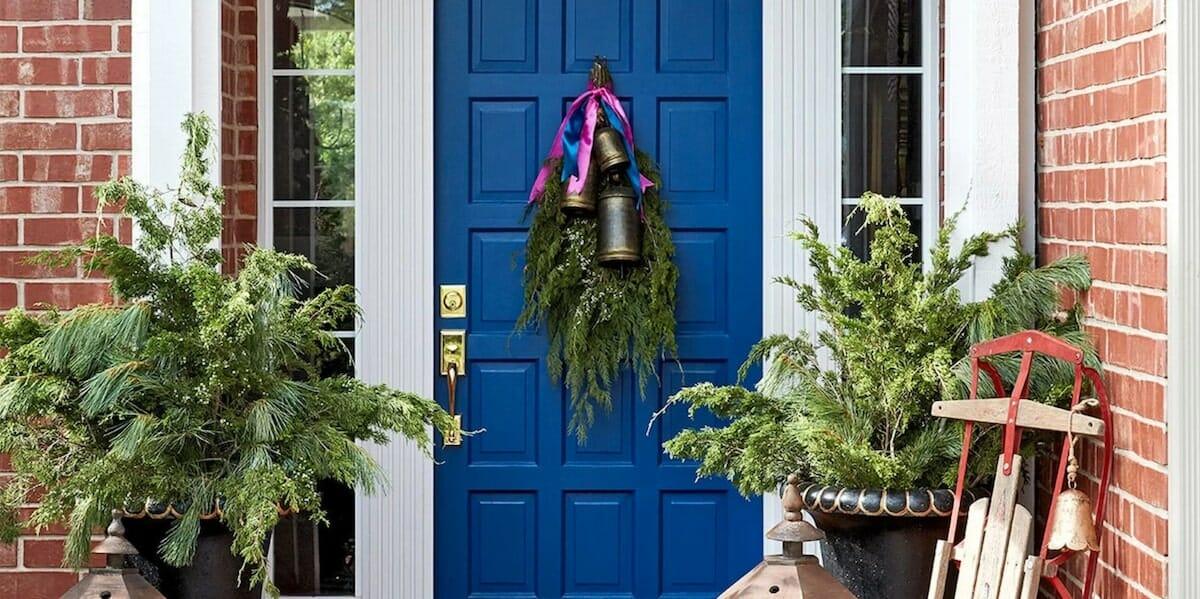 Evergreen fronds and bells winter door decoration