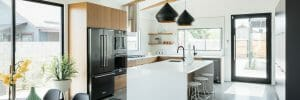 Contemporary white kitchen design with black pendants and white waterfall countertop and subway tiles