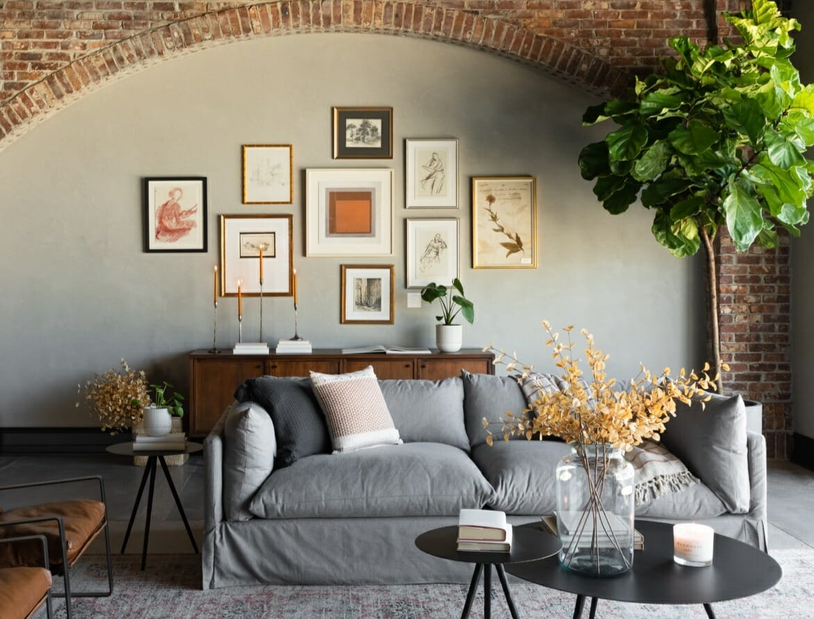 Living room with grey sofa and brick wall - haute bohemian