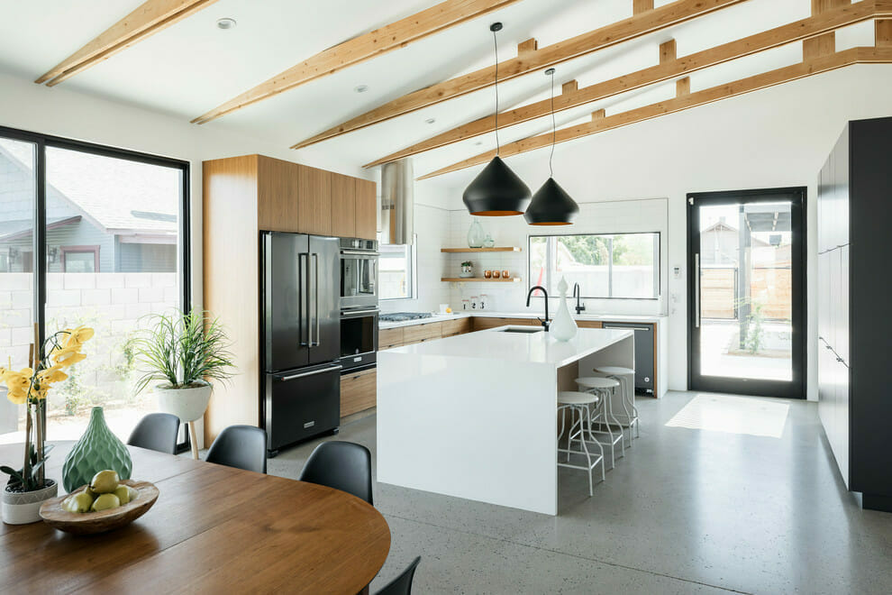Modern-white-kitchen-design-with-black-pendants-and-white-waterfall-countertop-and-subway-tiles